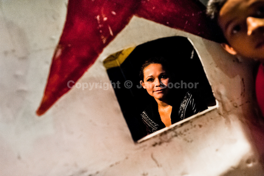 Bianca Rocio, a Salvadorean dancer, seen through a ticket office at the Circo Brasilia, a family run circus travelling in Central America, 10 May 2011. The Circo Brasilia circus belongs to the old-fashioned traveling circuses with a usual mixture of acrobat, clown and comic acts. Due to the general loss of popularity caused by modern forms of entertainment such as movies, TV shows or internet, these small family enterprises balance on the edge of survival. Circuses were pushed away and now they have to set up their shows in more remote villages. The circus art and culture is slowly dying in Latin America.