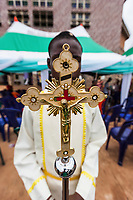 Nigeria. Enugu State. Enugu. St. Theresa's Parish. Catholic Church. A processional cross carried by an Igbo young man during the entrance procession of a Sunday catholic mass. A processional cross is a crucifix or cross which is carried in Christian processions. Collectively referred to as the Passion, Jesus' suffering and redemptive death by crucifixion are the central aspects of Christian theology concerning the doctrines of salvation and atonement. Enugu is the capital of Enugu State, located in southeastern Nigeria. 30.06.19 © 2019 Didier Ruef