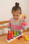 3 year old girl playing with color sorter matching colored rings to colored pegs, talking to herself