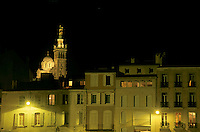 Illuminated exterior of Notre Dame de la Garde basilica seen at night from the Vieux-Port, Marseille, France.