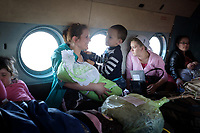 A woman flies home after giving birth at the Turukhansk district hospital, nearest hospital to her remote village. The government pays the cost of flights for pregnant women but the aircraft are standard unequipped vehicles used for many transportation services.