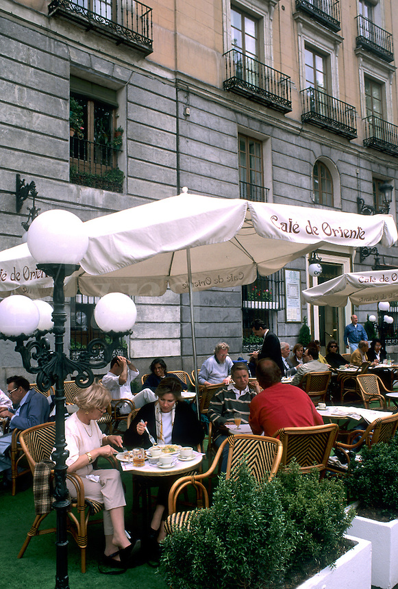 Life in Spain the Cafe de Oriente with tourists and umbrellas in Madrid Spain