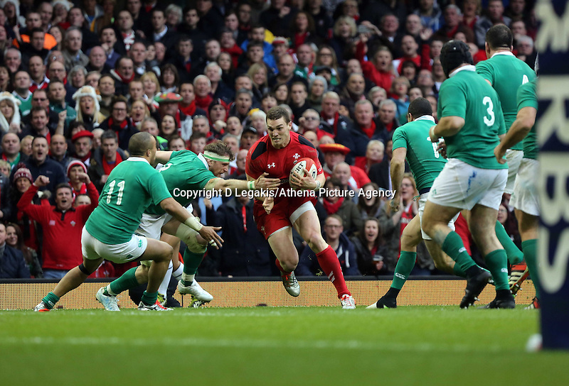 Pictured: George North of Wales (C) tries to avoid a tackle Saturday 14 March 2015<br /> Re: RBS Six Nations, Wales v Ireland at the Millennium Stadium, Cardiff, south Wales, UK.