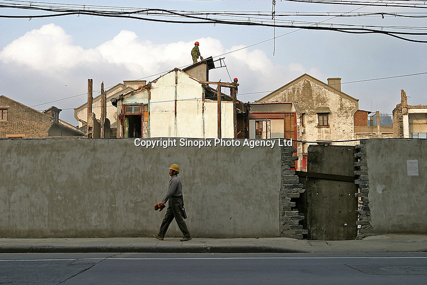 A construction worker passes in front of one of the many condemned areas currently being torn down in Old Town in Shanghai, China. Daily life is changing drastically for thousands in China as old neighborhoods are torn down to make way for new, modern structures..