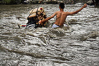 A contraband smuggler, facing wild waves, carries gasoline barrels through the river Tachira on the Colombia-Venezuela border, 3 May 2006. Venezuelan gasoline, being 20 times cheaper than in Colombia, is the most wanted smuggling item, followed by food and car parts, while reputable Colombian clothing flow to Venezuela. There are about 25,000 barrels of gasoline crossing illegally the Venezuelan border every day. The risky contraband smuggling, especially during the rainy season when the river rises, makes a living to hundreds of poor families in communities on both sides of the frontier.