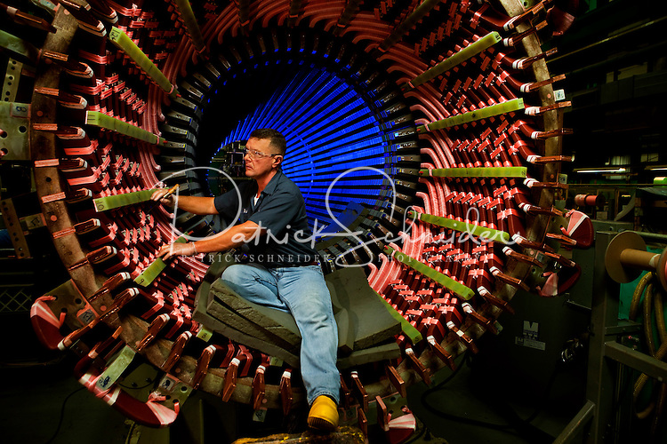 An employee of Siemens Charlotte Turbine-Generator Center in the Stator winding area inspects the electrical coils inside stator, which is the stationary part of a generator's rotor system. Siemens state-of-the-art generator manufacturing operations include new-unit generator manufacturing as well as service repairs for steam turbines and generators. The Charlotte NC manufacturing facility was founded in 1967 by Westinghouse Electric Corporation to manufacture nuclear low pressure turbines. Siemens Charlotte plant is the primary service center for generator and steam turbine equipment in the Americas, and the lead plant for manufacturing new electrical generators. Internationally, Siemens AG is Europe's largest engineering conglomerate.