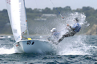 420 sailors crash through a small wave as they head out to sea.