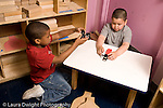 Education Preschool 4-5 year olds two boys talking and playing with small toy vehicles trucks and cars horizontal