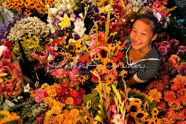 A teenage girl helps sell flowers at her family's flower stand in downtown Charlotte, NC. The family grows flowers on their North Carolina farm, then sells the fresh-cut flowers in bulk, as mixed-flower bouquets and as skillfully designed impromptu flower arrangements from under a tent on Tryon Street, a few blocks south of Charlotte's Square in the heart of downtown Charlotte. The florists operate their farmers-market-type flower stand most weekdays during the summer, serving customers who work in uptown Charlotte. In addition to offering shoppers good deals on fresh cut flowers, the flower growers are a bright oasis on Charlotte's city streets.