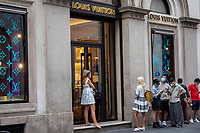 Milan, Italy , july 3 2021 - first day of summer sales - people waiting outside louis vouitton shop