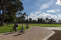 A man and two boys ride bikes along the paver pathway at South Gate Park, in front of a baseball field with people playing on it.