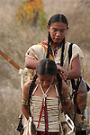 A Native American Indian teenager helping a younger boy by fixing his bone breast plate
