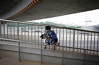 """CHINA. Beijing. A woman holds her baby near the 4th Ring Roag, near the new Olympic park. In recent years construction has boomed in Beijing as a result of the country's widespread economic growth and the awarding of the 2008 Summer Olympics to the city. For Beijing's residents however, it seems as their city is continually under construction with old neighborhoods regularly being razed and new apartments, office blocks and sports venues appearing in their place. A new Beijing has been promised to the people to act as a showcase to the world for the 'new' China. Beijing's residents have been waiting for this promised change for years and are still waiting, asking the question """"Where's the new Beijing?!"""". 2008"""