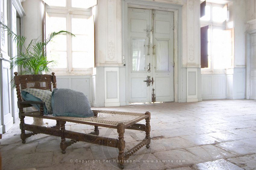 In the stately entrance hall: An old lounging chair chaise longue with a plant on the stone floor, walls painted white and soft sun light shining in through the windows. Chateau de Cerons (Cérons) Sauternes Gironde Aquitaine France