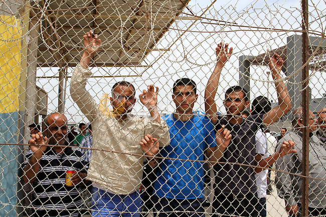 Palestinians stand behind fences as they wait their relatives coming from Egypt to the Gaza Strip through the Rafah border crossing between Egypt and southern Gaza Strip May 26, 2015. Egyptian authorities opened the Rafah crossing on Tuesday, for the first time in nearly 80 days, to allow stranded Palestinians to return to the Gaza Strip, witnesses and officials said. But it did not allow traffic the other way, leaving thousands of Gazans, some of whom need to travel for medical treatment, stuck inside the tiny enclave, authorities there said. Photo by Abed Rahim Khatib