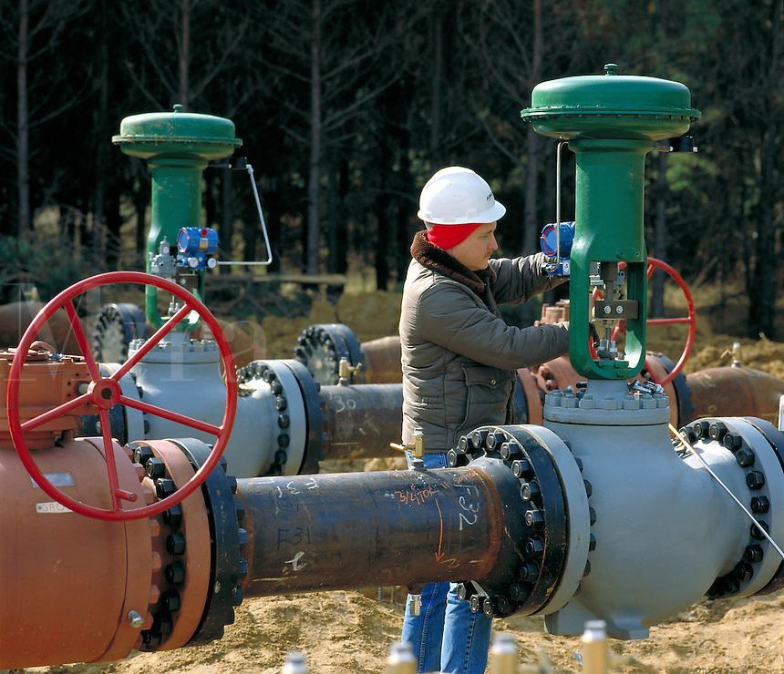 Construction worker checks installation of valves on new natural gas pipeline. Arkansas.