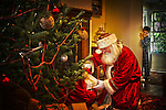 A little boy seeing Santa Claus putting presents under the Christmas Tree
