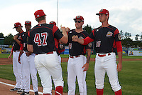Batavia Muckdogs Jordan Hillyer (47) fist bumps Connor Bach (35) and Marcus Crescentini (44) during introductions before a game against the State College Spikes on June 22, 2016 at Dwyer Stadium in Batavia, New York.  State College defeated Batavia 11-1.  (Mike Janes/Four Seam Images)