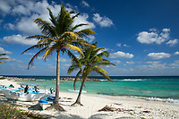Beautiful white sand beach with palm trees, small boats and the turquoise Caribbean Sea, near Laguna Columbia, south of Cozumel Island, Mexico