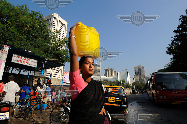 Slum dwellers collecting water from a public supply point in Cuffe Parade district in South Mumbai, which is also home to some of the city's most exclusive residential blocks, visible behind.