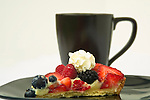 A berry fruit tart is on a black plate and is served with coffee in a black cup.