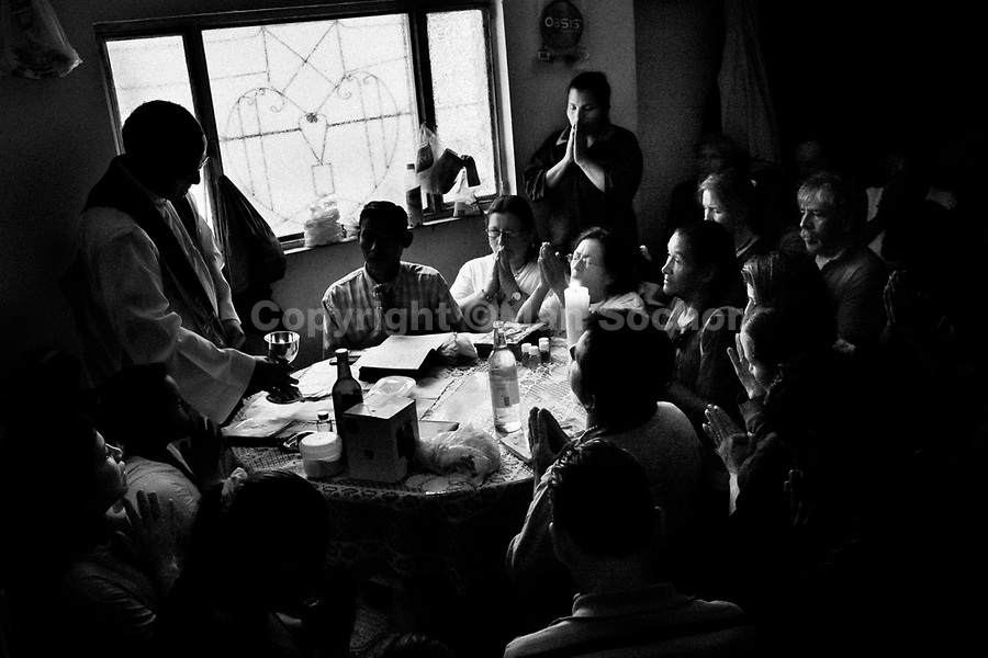 A Colombian pastor celebrates a liturgy before performing the healing ritual at a house church in Bogota, Colombia, 29 January 2013. Hundreds of Christian belivers, joined in nameless groups, gather every week in unmarked home churches dispersed in the city outskirts, to carry out prayers of liberation and exorcism. Community members and their religious activities are usually conducted by a charismatic pastor or preacher. Using either non-contactive methods (reading religous formulas from bible, displaying Christian symbols and icons) or rough body-pressure-points techniques and forced burping, a leading pastor commands the supposed evil spirit, which is generally believed to come from witchcraft, to depart a person's mind and body. The demon's expulsion often consists of multiple rites and may last for several months.