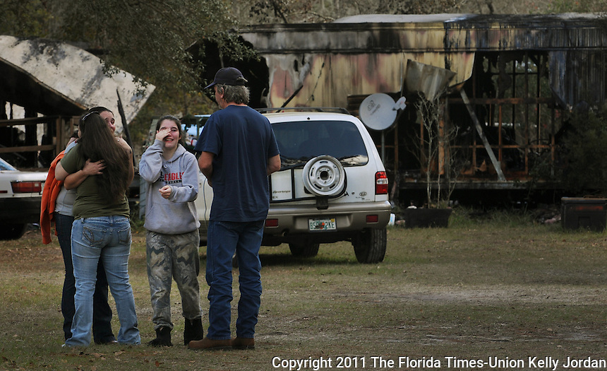 Kelly.Jordan@jacksonville.com--123111--Family comforts each other after a fire that killed a four year-old boy and a 66 year-old man who lived in the home at 2410 Gladiolus Avenue in Middleburg Saturday morning, December 31, 2011.A 14 year-old girl, second from right, survived the fire and tried to get her brother and grandfather out, but the structure was already too involved and she could not get them out.(The Florida Times-Union, Kelly Jordan)