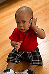 12 month old baby boy sitting on floor holding cell telephone to ear pretend play talking