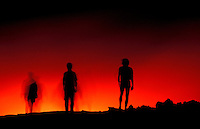 Three people are silhouetted against a background of fiery red from Kilauea Volcano on the Big Island of Hawaii.