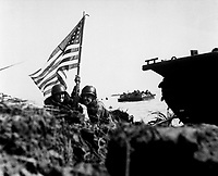 First flag on Guam on boat hook mast.  Two U.S. officers plant the American flag on Guam eight minutes after U.S. Marines and Army assault troops landed on the Central Pacific island on July 20, 1944. Batts. (Marine Corps)<br /> NARA FILE #:  127-N-88073<br /> WAR & CONFLICT BOOK #:  1177
