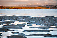 Sunset at Okarito Lagoon with tidal pools and Southern Alps hiding in clouds, Westland Tai Poutini National Park, UNESCO World Heritage Area, West Coast, New Zealand, NZ