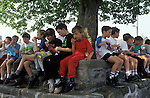 Bellerby Feast,  Bellerby Yorkshire UK. Local children around the village tree have a snack before the mid day fancy dress competition. Which I judged. 1980s.