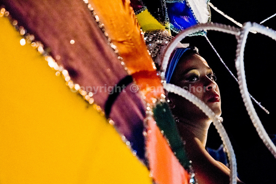 A Cuban girl waits behind the colour decorated float during the Carnival in Santiago de Cuba, Cuba, 25 July 2008. Carnival in Santiago de Cuba is a large public celebration which is held - contrary to the other Latin American carnivals - in the summer. The carnival tradition dates back to the 17th century when the Spanish festival of Santiago (St. James) was mixed with street dancing parades of the Black African slaves. Nowadays comparsas, carnival groups of dancers and musicians, flow in the streets and perform popular music like salsa, rumba or reggaeton. In spite of the general lack of funds in Cuba (most of the festival costumes and floats are home-made) the Carnival is very lively and hot show with huge participation of the people of Santiago de Cuba.