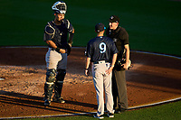 Tampa Tarpons coach Ryan Hunt (9) questions a call with umpire Kenny Jackson as catcher Antonio Gomez (5) looks on during Game Two of the Low-A Southeast Championship Series against the Bradenton Marauders on September 22, 2021 at LECOM Park in Bradenton, Florida.  (Mike Janes/Four Seam Images)