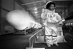 """A small boy wearing an oversize NASA space suit while being photographed besides the Chinese """"Long March Number 3"""" rocket, at the Zhongshan Park rocket exhibition. Shanghai, the Peoples Republic of China. 2000"""