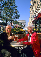 Retired senior couple having a beer on the most famous streets in the world Champs Elysees in Paris france with Arc de Triomphe in background