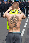 © Joel Goodman - 07973 332324 . 03/09/2011 . London , UK . An EDL supporter with a crusader tattoo on his back photographs the rows of police assigned to keep the EDL demonstration out of Tower Hamlets and away from the East London Mosque . The English Defence League hold a rally in Aldgate, near Tower Hamlets in East London. The group had intended to march however the Home Secretary banned all marches in the area. Photo credit : Joel Goodman
