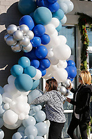 Business partners Marisa Scott (left) and Nikki Lee, with Confetti NWA of Fayetteville, suspend a large balloon garland Tuesday, November 17, 2020, on the storefront of Linden's Jewelry. Linden's is celebrating a grand re-opening after relocating their store from Bella Vista to Bentonville. Check out nwaonline.com/201118Daily/ and nwadg.com/photos for a photo gallery.(NWA Democrat-Gazette/David Gottschalk)
