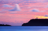 A long exposure at Secrets Beach sees the beacon flash and the silhouette of the Kilauea lighthouse under a pink dawn sky.