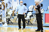 CHAPEL HILL, NC - FEBRUARY 24: Head coach Roy Williams of North Carolina talks with official Brian Dorsey during a game between Marquette and North Carolina at Dean E. Smith Center on February 24, 2021 in Chapel Hill, North Carolina.