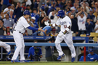 Yasiel Puig #66 of the Los Angeles Dodgers is greeted by Dodgers third base coach Tim Wallach #26 after hitting a grand slam home run during a game against the Atlanta Braves at Dodger Stadium on June 6, 2013 in Los Angeles, California. (Larry Goren/Four Seam Images)