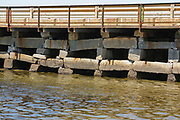 Bailey Island Bridge in Harpswell, Maine USA, which is on the New England seacoast. The bridge is 1,150-foot long and was built in 1928. It connects Bailey Island and Orr's Island, plus it is listed on the National Register of Historic Places. It is believed to be the only granite cribstone bridge left in the world today.