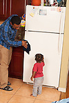 17 month old toddler boy helping father clean in kitchen