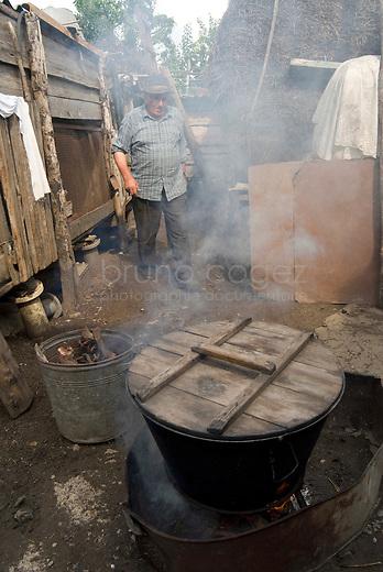 REPUBLIC OF MOLDOVA, Gagauzia, Vulcanesti, 2009/06/30..Pantel Kirilovitch CERNEVES, the stepfather of Viera, prepares cascaval, cheese cooked in the backyard of the house..© Bruno Cogez..REPUBLIQUE MOLDAVE, Gagaouzie, Vulcanesti, 30/06/2009..Pantele Kirilovitch Cernev, le beau père de Viera, prépare le cascaval, fromage à pâte cuite, dans l'arrière cour de la maison..© Bruno Cogez