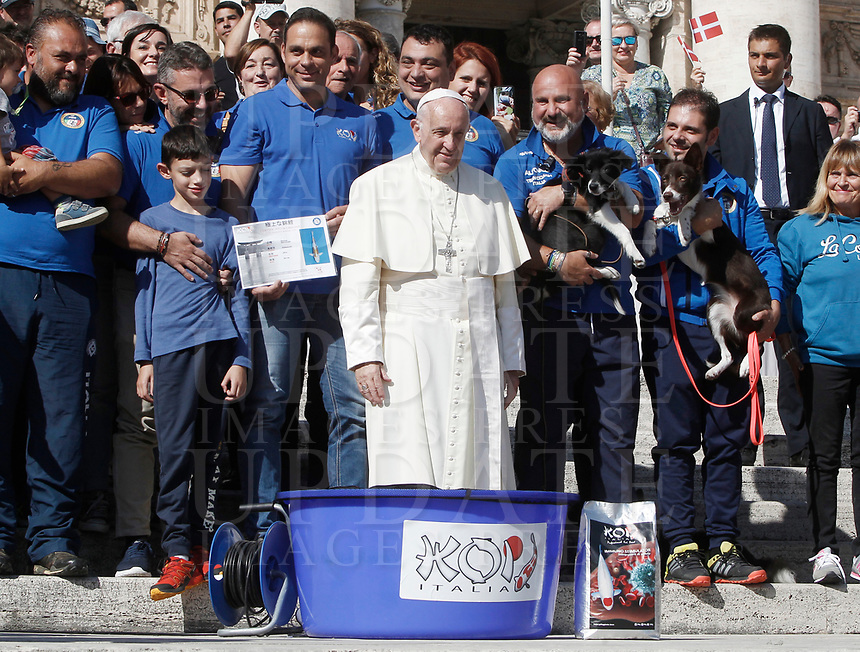 Papa Francesco posa con alcuni membri della Federazione Italiana sport cinofili durante l'udienza generale del mercoledi' in Piazza San Pietro, Citta' del Vaticano, 4 ottobre, 2017.<br /> Pope Francis poses with members of a dog training unit during his weekly general audience in St. Peter's Square at the Vatican, on October 4, 2017.<br /> UPDATE IMAGES PRESS/Isabella Bonotto<br /> <br /> STRICTLY ONLY FOR EDITORIAL USE