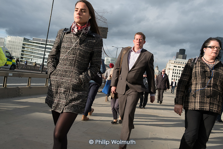 City of London workers walk across London Bridge.