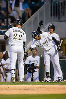 Matt Davidson (22) of the Charlotte Knights slaps hands with teammate Engel Beltre (7) after hitting a home run against the Norfolk Tides at BB&T BallPark on April 9, 2015 in Charlotte, North Carolina.  The Knights defeated the Tides 6-3.   (Brian Westerholt/Four Seam Images)