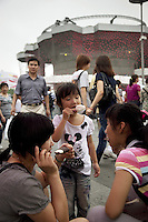 China. Shanghai. World Expo. Expo 2010 Shanghai China. Outside Switzerland Pavilion. A young girl - wearing a tee shirt with Walt Disney Characters, Minnie Mouse - eats an ice cream with her sisiter and her mother who is using a mobile phone. Cloudy sky. 27.06.10 © 2010 Didier Ruef
