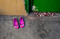 A pair of pink pumps is seen taken off in front of a room where sexual services are offered to clients in San Salvador, El Salvador, 21 February 2014. Although prostitution is not legal in El Salvador, dozens of street sex workers, wearing provocative miniskirts, hang out in the dirty streets close to the capital's historic center. Sex workers of all ages are seen on the streets but a significant part of them are single mothers abandoned by their male partners. Due to the absence of state social programs, they often seek solutions to their economic problems in sex work. The environment of street sex business is strongly competitive and dangerous, closely tied to the criminal networks (street gangs) that demand extortion payments. Therefore, sex workers employ any tool at their disposal to struggle hard, either with their fellow workers, with violent clients or with gang members who operate in the harsh world of street prostitution.