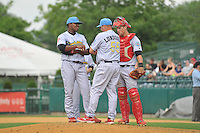 Pitching coach Dave Lundquist (55) of the Reading Fightin Phils visits with Pitcher Perci Garner (10) and catcher Logan Moore (15) during a game against the New Britain Rock Cats at New Britain Stadium on July 13, 2014 in New Britain, Connecticut.  (Gregory Vasil/Four Seam Images)